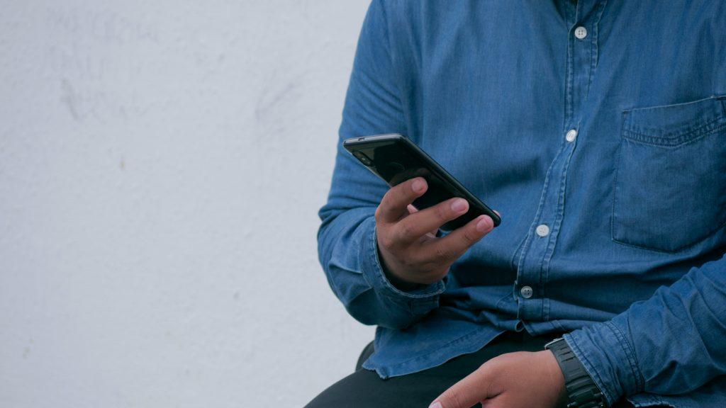 person in blue denim jacket holding smarthone